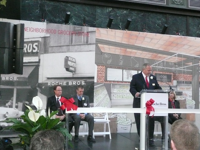 Gary Pfeil, Roche Bros. president, delivers opening remarks Wednesday at the grocer's Downtown Crossing store debut with Roche Bros. owners Ed and Rick Roche, sitting. The panoramic in the background details the first Roche Bros. store in Boston's Roslindale neighborhood in 1952.
