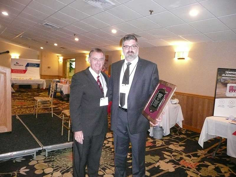 NHGA President John Dumais presents the Supermarket of the Year Award to Ed Penta of McKinnon's Market.