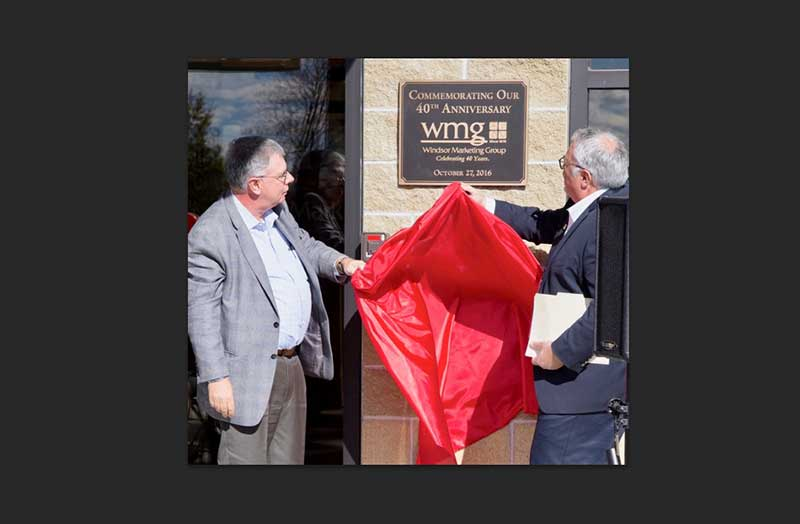 Windsor Marketing Group founder and CEO Kevin Armata and CMO Steve Thomas unveil the anniversary plaque on the new building.