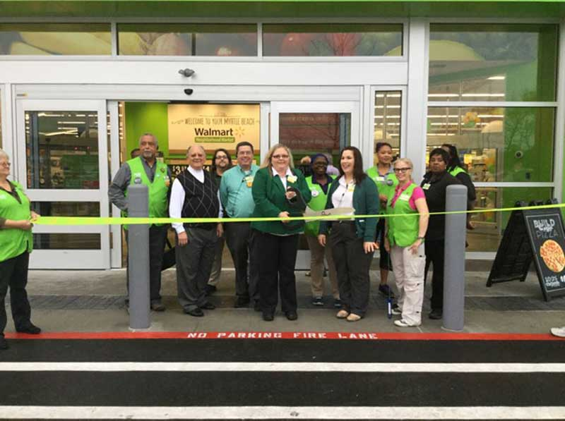 Store manager Sherrie Carlisle cuts the ceremonial ribbon on the new Walmart Neighborhood Market in Myrtle Beach.