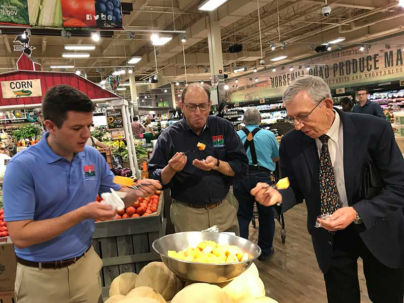 New Jersey Agriculture Secretary Douglas H. Fisher, center, samples Jersey Fresh cantaloupe at the ShopRite of Greater Morristown with Bob Sumas, right, president of Village Super Market Inc., and Tom Beaver, director of marketing and development for the New Jersey Department of Agriculture.