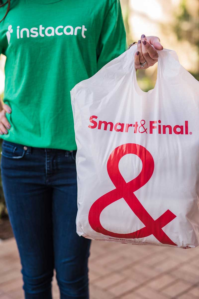 Instacart shopper carries Smart & Final bag for delivery.