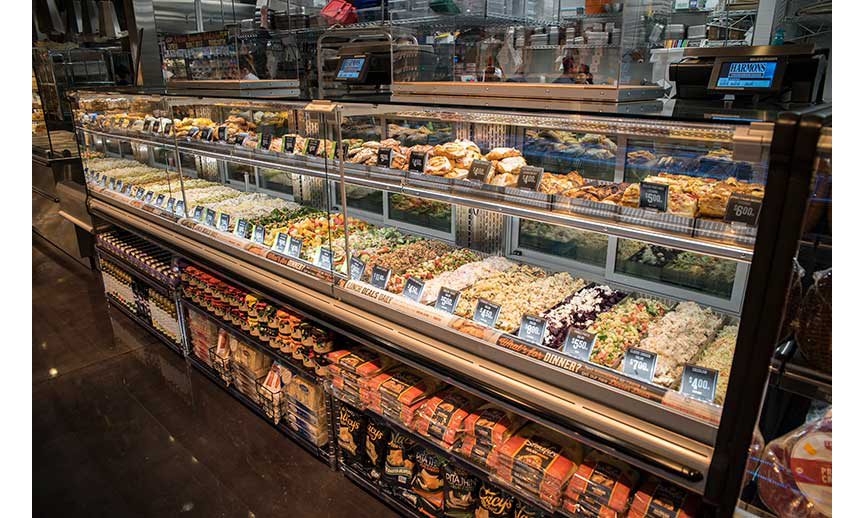 """The Harmons Holladay Market in Holladay, Utah, features a Lunch Deals Daily and """"What's for Dinner?"""" case that holds a range of by-the-pound prepared foods and bakery items as well as center store items down below."""