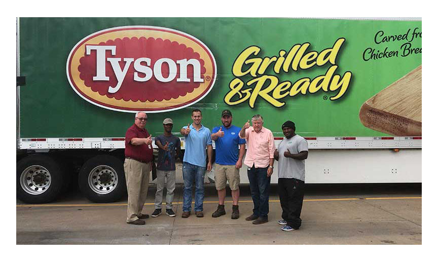 A group of men giving the thumbs up sign in front of a Tyson truck