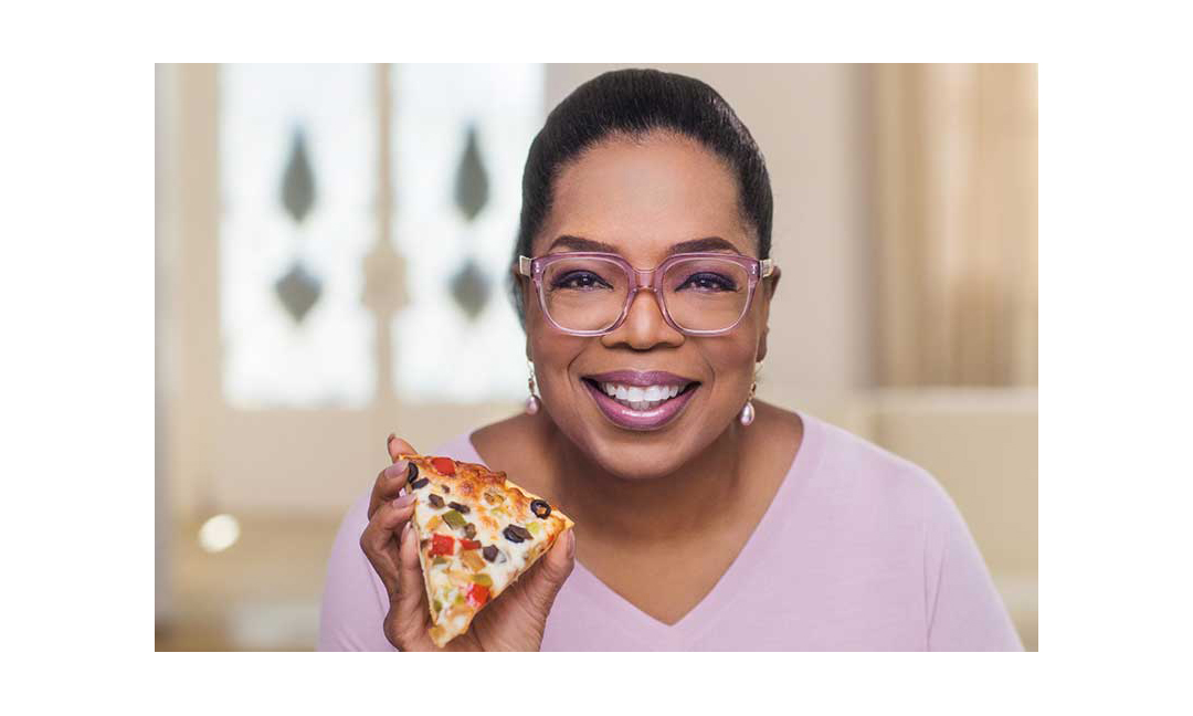 Oprah with a slice of her branded frozen pizza