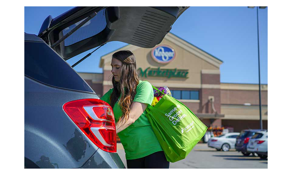 An Instacart shopper loading a car in a Kroger parking lot.