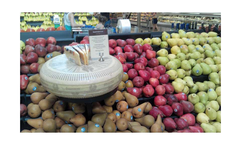 A produce department displaying cheese with the fruit