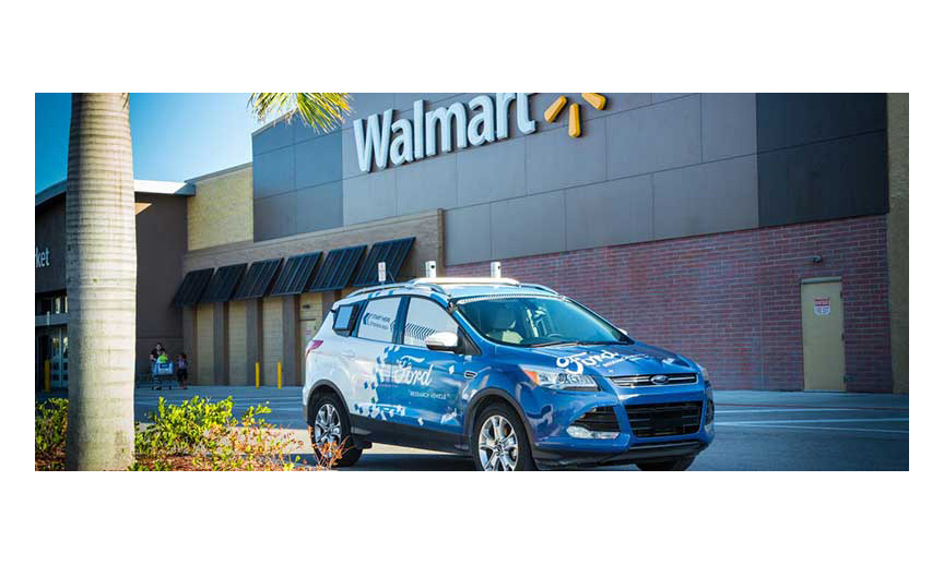 A driverless Ford car in front of a Walmart