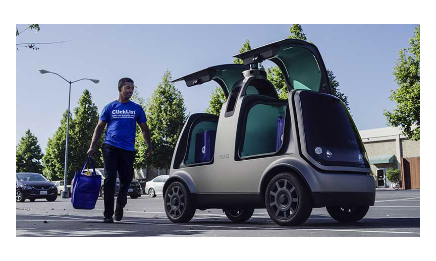 A Kroger employee loading a Nuro autonomous delivery vehicle.