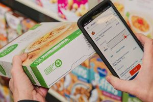 A woman scanning a cereal box with her smartphone