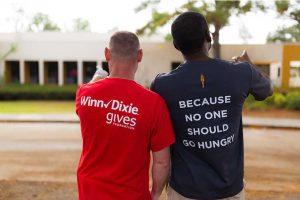 A Winn-Dixie and Feeding America representative show off their promotional t-shirts