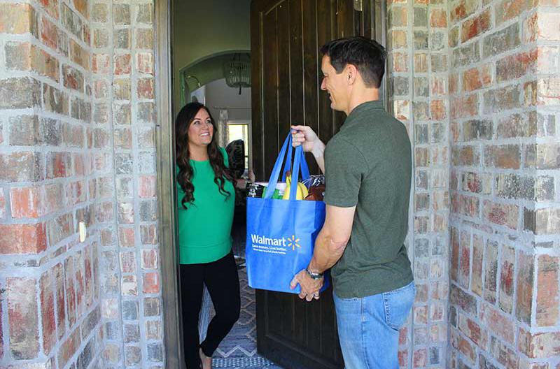 A man handing Walmart groceries to a woman at her front door.