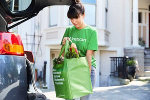 An Instacart shopper with a bag of groceries
