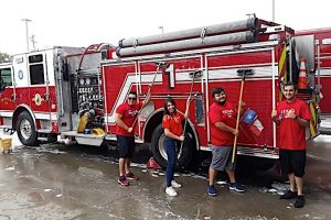 H-E-B employees washing a fire truck