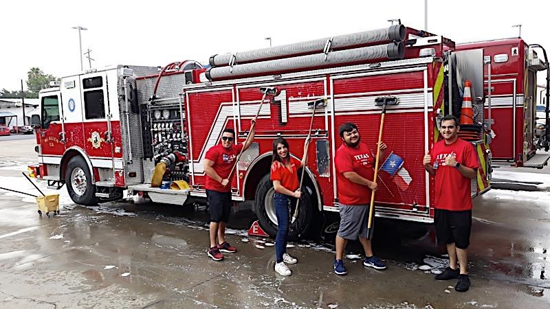 H-E-B employees washing a fire truck