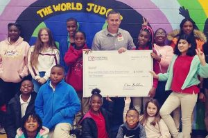 Tom Condon, GM of BJ's Wholesale Club in Pensacola, Florida (center), presents a $10,000 donation from the BJ's Charitable Foundation to the Boys and Girls Clubs of the Emerald Coast on Dec. 17, 2019.